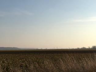 Vlak akkerlandschap met watertoren in de verte.