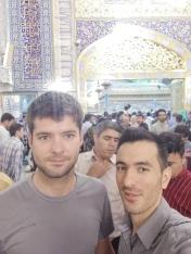 Amin en ik, met de graftombe van Imam Reza in de achtergrond.