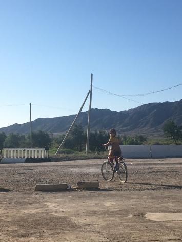 Oezbeeks meisje op een veel te grote fiets.