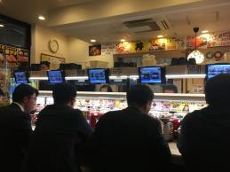 Mannen in suit aan de sushi band. Typisch Japans beeld.